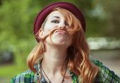 picture of moustache  - Hipster redhead woman making a moustache with her hair outdoor - JPG