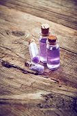 stock photo of gels  - Bottles with purple shower gel and sea salt on wooden background - JPG
