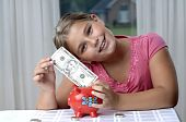 stock photo of little school girl  - School girl is playing with a paper bills before putting them into the piggy bank - JPG