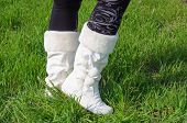 stock photo of thigh highs  - Legs in black stockings and white boots on green grass - JPG
