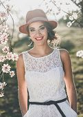 foto of wearing dress  - Portrait of young woman in the flowered garden in the spring time - JPG
