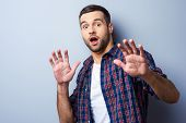 foto of terrifying  - Frustrated young man in casual shirt keeping mouth open and looking terrified while standing against grey background - JPG