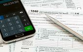 pic of irs  - USA tax form 1040 for year 2014 with a pen and calculator app on smartphone illustrating completion of tax forms for the IRS - JPG