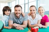 stock photo of family bonding  - Happy sporty family bonding to each other while lying on exercise mat together - JPG