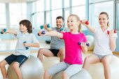 stock photo of physical education  - Happy sporty family exercising in sports club together - JPG