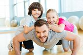 picture of physical education  - Happy little children bonding to their father doing push - JPG