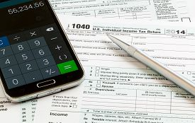 image of irs  - USA tax form 1040 for year 2014 with a pen and calculator app on smartphone illustrating completion of tax forms for the IRS - JPG