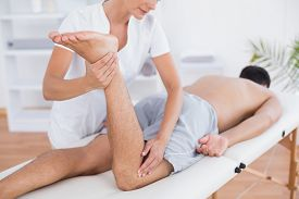 image of physiotherapist  - Physiotherapist doing leg massage to her patient in medical office - JPG