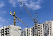 picture of construction crane  - Construction cranes on a background of blue sky and houses under construction - JPG
