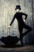 picture of top-hat  - Elegant male mime artist in top hat posing with umbrella by a grunge wall - JPG