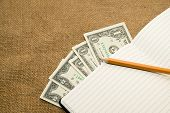 picture of memento  - Opened notebook with a blank sheet pencil and money on the old tissue - JPG