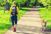 Woman Runner Walking With Dog In Summer Park poster