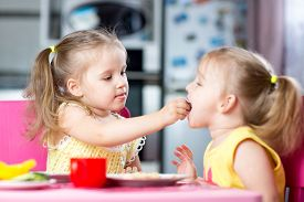 image of little sister  - Two little children toddlers eating meal together one girl feeding sister in sunny kitchen at home - JPG