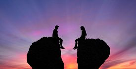 stock photo of conflict couple  - Young couple in quarrel sitting on rocks shaped as broken heart - JPG