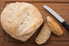 image of home-made bread  - knife and home made bread on wooden board  - JPG