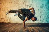 Young man break dancing on wall background. Vibrant colors effect. Tattoo on body. poster