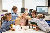 education, children, technology, science and people concept - group of happy kids building robots an poster