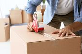 House moving concept. Closeup of man packing cardboard box poster