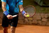 A tennis player prepares to serve a tennis ball during a match poster