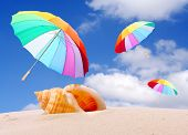 stock photo of end rainbow  - Tropical beach with rainbow umbrellas flying in stormy wind - JPG