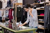 Young businesswoman checking laptop in her clothing store. Young entrepreneur using laptop and talki poster