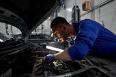 car service, repair, maintenance and people concept - auto mechanic man with lamp working at worksho poster