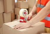 Closeup of man packing parcels with sticky tape at warehouse poster