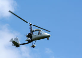 image of ultralight  - A ultralight helicopter being flown above the clouds - JPG