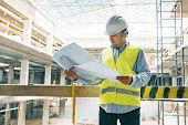 Portrait Of Male Engineer At Construction Site. Builder Looks At The Plan Of The Construction Site.  poster