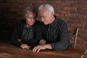 Poor Elderly Couple Counting Coins At Table poster