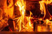 Firewood Burning In Fire Burns In The Fireplace. The Brick Oven Gives Heat And Heat From The Burnt L poster