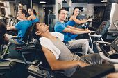 A Man Is Tired After Physical Training On Cardio. Men And Women Perform Physical Exercises On Cardio poster