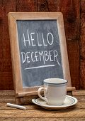 Hello December sign - white chalk handwriting on a blackboard with a cup of coffee against rustic ba poster
