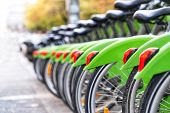 Blur Background Of Public Rental Bicycles Standing In Row On Street. Green Rental Bikes On Parking D poster