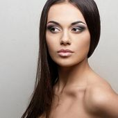 Portrait of beautiful young woman with long straight brown hair, isolated on white background