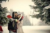 Couple In Love With Red Santa Claus Hat In Winter. New Year Girl And Guy In Snowy Forest. Winter Hol poster