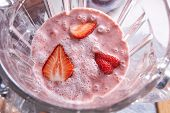 Homemade healthy smoothie dessert with strawberry pieces in a blender bowl. Top view poster