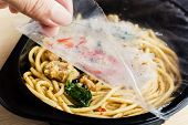 Food Delivery Service: Woman Hands Holding Open Cling Wrap And Take Out Food In Plastic Boxes On Woo poster