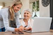 Smiling mature woman making payment via credit card for shopping done by senior woman at home. Elder poster