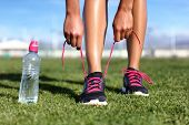 Start training healthy active lifestyle concept- Runner girl getting ready to exercise on grass tyin poster