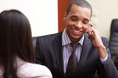 Happy african-american businessman on phone in office