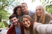 Multi ethnic group of five young adult friends pose to camera while taking a selfie during a break i poster