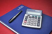 stock photo of cpa  - Business Books Calculator Expenses Bookkeeping Pen on top of blue spiral bound monthly accounting income and expense reports with deep red background - JPG