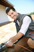 foto of gutter  - Roofer working on house roof to fix gutter - JPG