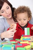woman and toddler playing with wooden construction game