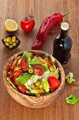 picture of iceberg lettuce  - Bowl made of olive wood filled with cos and iceberg lettuce salad with paprica carrots tomatoes and green olives on wooden table - JPG
