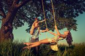 stock photo of board-walk  - Beautiful mom on the swing in the forest with her family - JPG