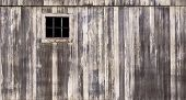 stock photo of woodgrain  - Rustic barn with weathered wood and small window - JPG