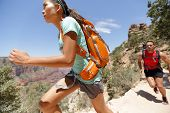 Trail runner woman in cross country running race in Grand Canyon. Couple training working out togeth