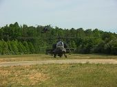 foto of apache  - Apache Helicopter spinning up on a grass airfield - JPG